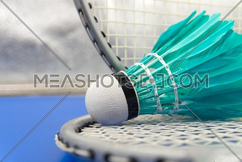 Badminton feather shuttlecocks in green with badminton rackets in a close up view