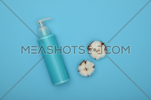 Close up one bottle of shower gel, shampoo or body care beauty product and white cotton flower over pastel blue background, elevated top view, directly above