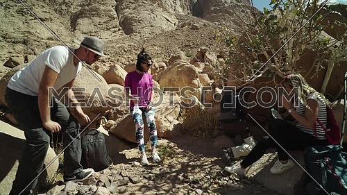 Follow shot for group of tourists get rest in the shade besides Almond tree with bedouin guide and eating almonds to explore Sinai Mountain for wadi Freij at day.