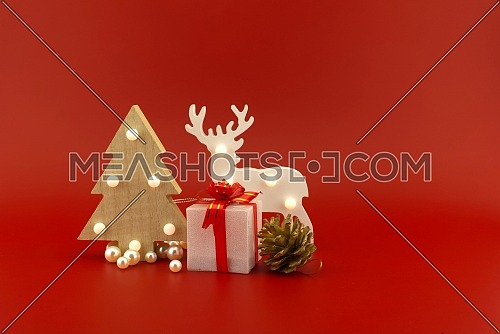 Christmas tree and gift box with wooden reindeer or elk ornament and copy space for text on a festive red background. New Year and Christmas holiday season concept card decoration