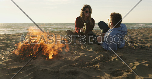 Young Couple Relaxing By The Fire, Drinking A Beer Or A Drink From The Bottle.