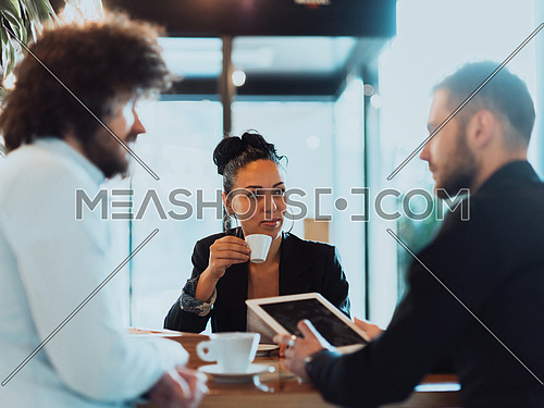 A group of people on a coffee break use laptops, tablets, and smartphones while talking about new business projects