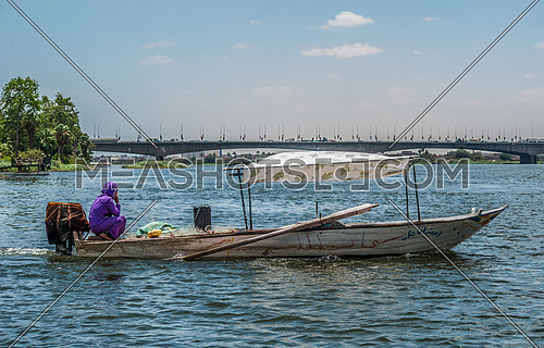 A girl sitting in a fishing boat in the middle of the Nile