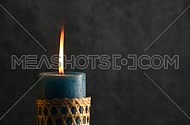 Blue candle with straw twigged holder trembling flame close up out of the grey background, off-center, focusing in and blown out