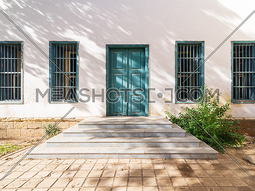 White marble stair in front of white wall with green wooden old grunge decorated door and four wrought iron windows