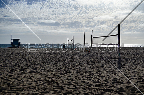 Volleyball nests set on the beach reach for a match