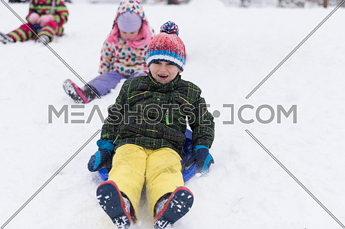 group of kids having fun and play together in fresh snow on winter vacation
