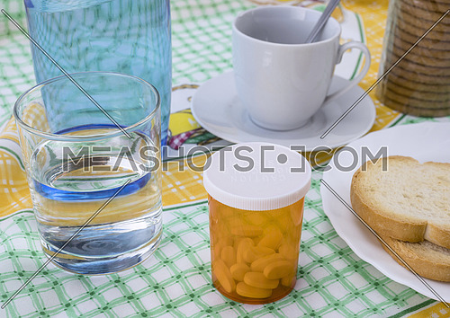 Medication during breakfast, capsules next to a glass of water, conceptual image, horizontal composition