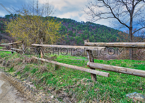 Old wooden fence, trees, green grass, and blue cloudy sky on green meadow, Mudurnu, Turkey