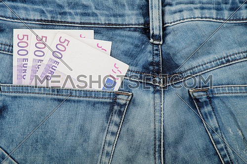 Close up several five hundred Euro paper currency banknotes in jeans back pocket, low angle view
