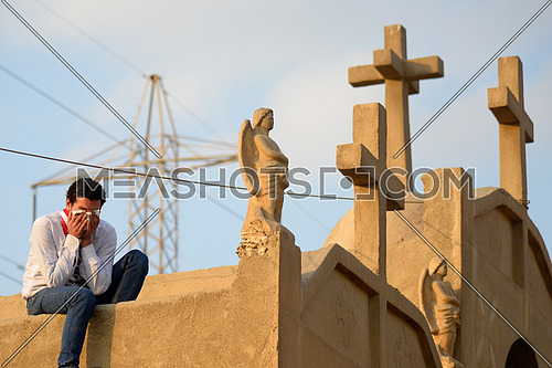 A young man cries during the burial of victims of the Egyptian al Botrouseya church bombing in Egypt