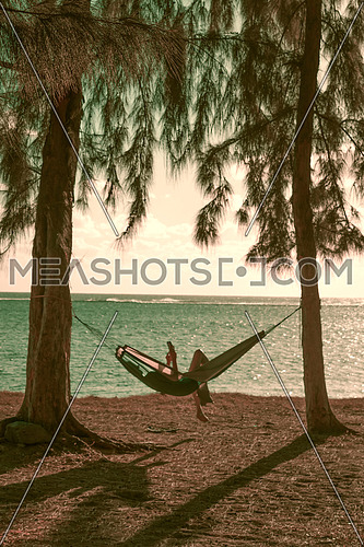 Silhouette of woman reading in hammock,used split toning effect,vertical photo.