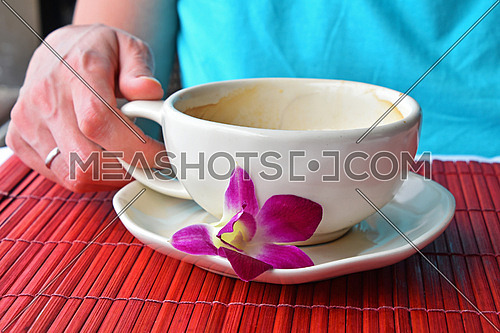 Woman hand holding half empty latte coffee cup with orchid flower at porcelain saucer