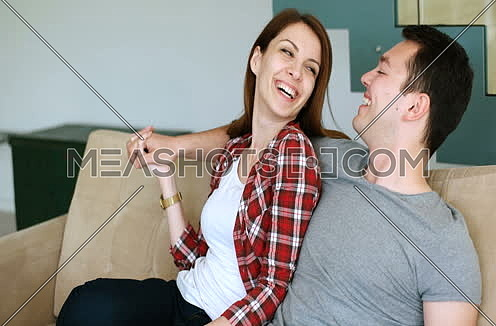 Young couple watching tv in the living roonm