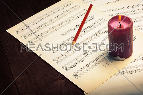 In the picture lit candle , aged pages of sheet music, pencil and wooden background,used split tonig for old/vintage style.