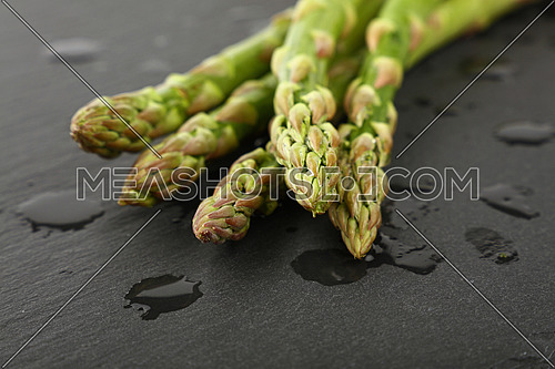 Fresh green asparagus washed on black slate board with drops of water, close up, low angle view