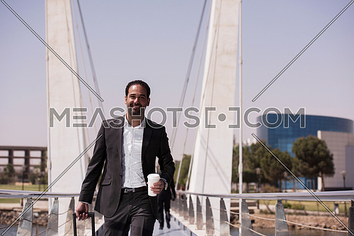 businessman walking with his suitcase at airport terminal and drink fresh morning coffee