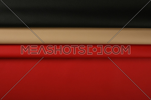 Close up background of black, red and beige white natural leather grain, directly above
