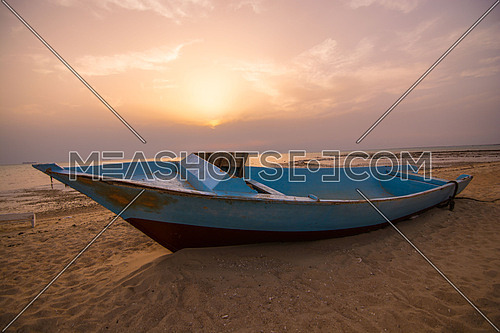 An abandoned boat on a sand beach
