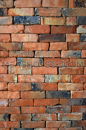 Rough red brown brick wall background texture without cement close up, side view