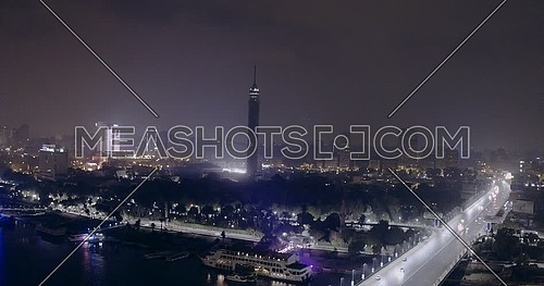 Aerial shot flying backward Cairo Tower showing the river Nile and 15 Off May Bridge at night