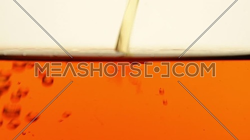 Stream of red black tea poured in transparent glass teapot, air bubbles flow when filling, slow motion, extreme close up, low angle side view
