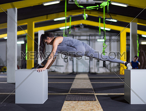 young athletic woman doing gymnastic exercise between two fit boxes at crossfitness gym