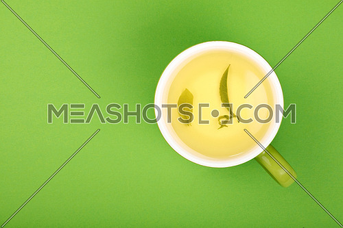 One full freshly brewed green oolong tea in big cup with saucer with leaves floating on green paper background, top view, point of view, detail close up