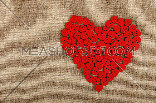Red heart shaped handmade wooden sewing buttons on linen canvas with copy space left, elevated top view