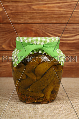 Close up of one glass jar of pickled small gherkin cucumbers checkered linen textile fabric lid decoration and green ribbon on canvas over brown wooden background, low angle side view