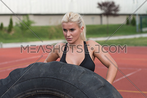 Young Woman Turning Tire Over - Bodybuilding Exercises Truck Tire