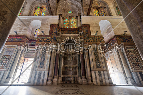Mausoleum of Sultan Qalawun with decorated colorful marble niche (Mihrab) embedded in ornate marble wall, and colorful stain glass windows, Moez Street. Cairo, Egypt