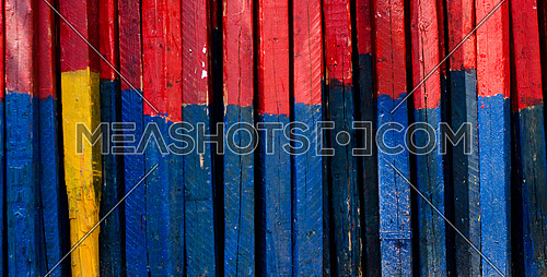 A background of colored wooden boards, half blue and half red and one in yellow.