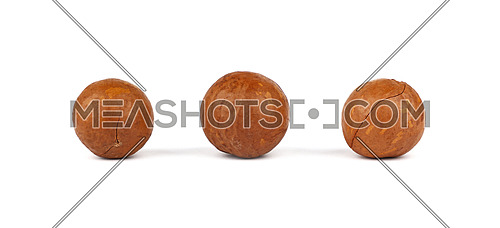 Close up three macadamia nuts isolated on white background, low angle side view