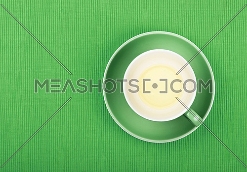 Empty cup of clear green tea on bottom at saucer over green textile tablecloth, close up, elevated top view