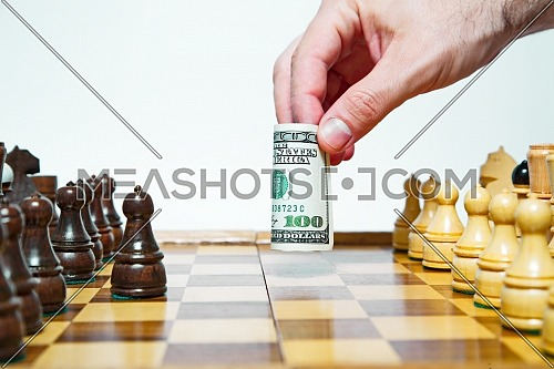 Man plays chess with hundred dollars bill and makes move