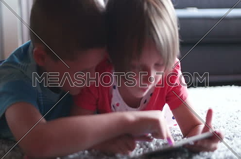 children using tablet at home on carpet
