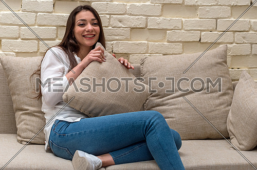 A young woman sits alone at home