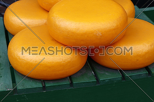 Close up big yellow wheels of hard matured gouda Dutch cheese, high angle view