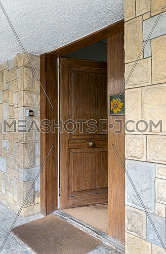 Half opened front wooden door at a stone bricks colored wall and a brown doormat