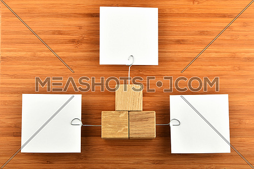 Different Opinions - Three white paper notes with wooden holders in different directions on bamboo wooden background for presentation