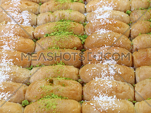 Baklava, traditional oriental sweet pastry cookies with pistachio and coconut  in retail market display, close up, high angle view