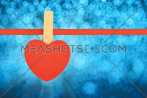 Valentine day template, one red wooden heart with clothes pin on textile ribbon over winter snow blue glitter blur