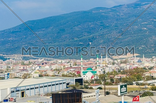 Landscape of a Turkish city by the ocean showing the buildings and stores, signs and billboards and a mosque by a big mountain - Turkey -November 2018