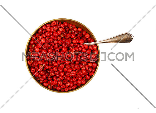 Close up one bronze metal bowl full of red pink pepper peppercorns with spoon isolated on white background, elevated top view, directly above