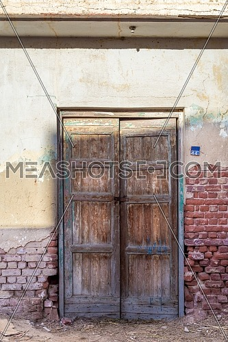 Closed wooden weathered door and shabby old grunge red bricks wall on abandoned district
