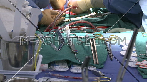 Close shot for surgical tray with surgical instruments and performing surgery in background
