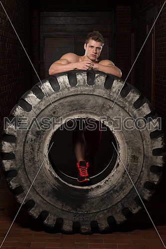 Young Muscular Man with Truck Tire Resting Afther Doing Crossfit Style Workout Turning Tire Over