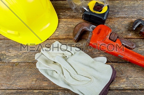 Working gloves, building helmet and glasses, work tool equipment on wood table