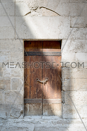 Wooden aged door and stone wall at Bebars Mosque, Medieval Cairo, Egypt